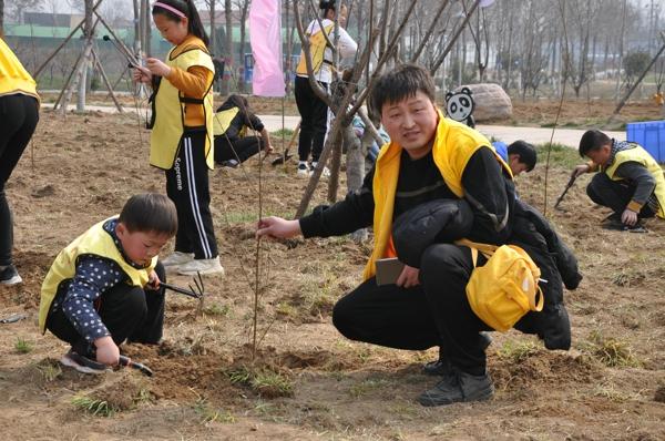 """郑州市红领巾成长营开展""""护绿新希望,我与小树共成长""""植树活动"""